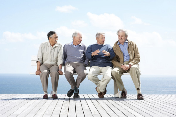 Portrait of a group of male mature friends sitting together on bench by the ocean - Outdoor